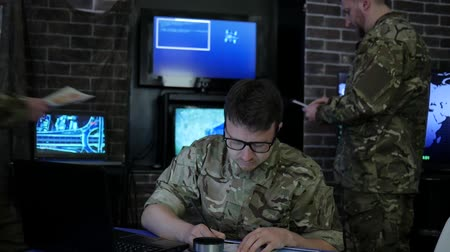 safeness : portrait professional soldier in uniform, in computer center war, martial law and battle tactics, safety system, on background dispatch room, beside computer and employees Stock Footage