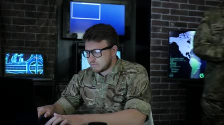 safeness : portrait pro soldier in glasses, in control room, working for laptop, search safety system, briefing specialists, on background multiple displays and group people discussing battle strategy