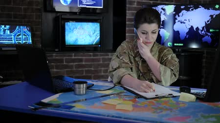 отправка : portrait pro officer female in camouflage uniform, working with laptop and talking on mobile phone, in military base, system tracking terrorists, briefing, on background multiple displays and world map Стоковые видеозаписи