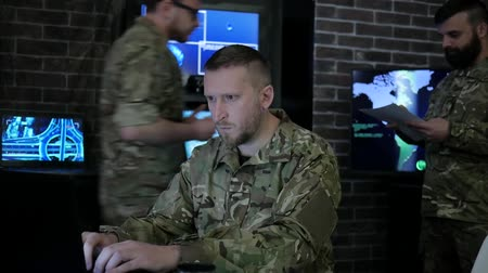 safeness : portrait officer men in camouflage uniform, in system control center, cyber security, tracking safeness, terrorists tracking system, on background Workstation, monitor and employees, War headquarters