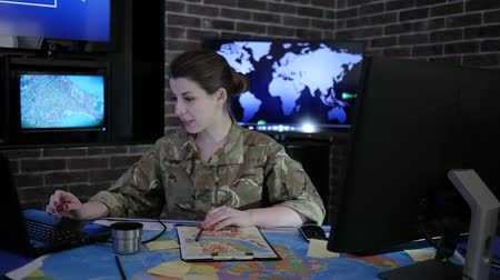 командир : portrait feminine professional officer in camouflage uniform, in system control center, working video chat, discussing battle strategy, on background multiple displays, Military headquarters Стоковые видеозаписи