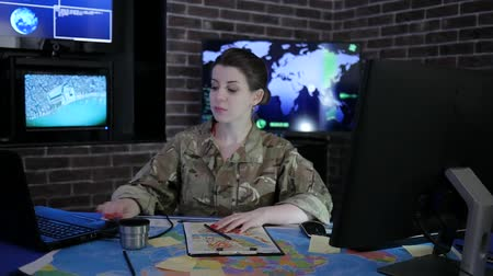 safeness : portrait Military personnel female pro soldier in uniform, in monitoring room, working video chat, discussing battle strategy in laptop, system tracking terrorists, on background multiple displays Stock Footage
