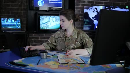 командир : portrait experienced officer woman in camouflage uniform, in military base, War center, working for laptop, system tracking terrorists, briefing, on background multiple displays and world map