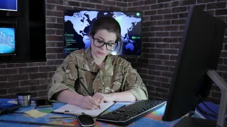 safeness : girl portrait soldier in glasses and uniform, working with computer, in system control center, cyberterrorism and searches safety system, Looks at camera, on background displays and world map