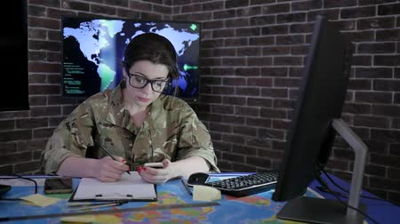 командир : Military personnel girl portrait soldier in glasses and camouflage uniform, working with laptop and mobile phone, computer center, safety system tracking terrorists, background displays and world map Стоковые видеозаписи