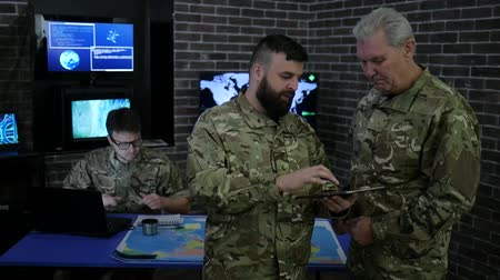 komutan : War center, general and officer, in military headquarters, view digital tablet, discussing assault, security service and tracking terrorists, in background team and screen monitors and computer Stok Video