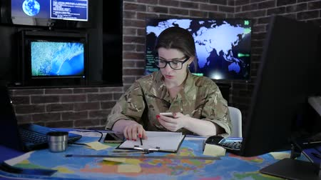 командир : female pro officer portrait in camouflage uniform, working with laptop and mobile phone, in military base, system tracking terrorists, briefing, on background multiple displays and world map