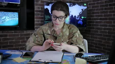safeness : female portrait officer in glasses and uniform, working with laptop and mobile phone, in military base, safety system tracking terrorists, on background multiple displays and world map
