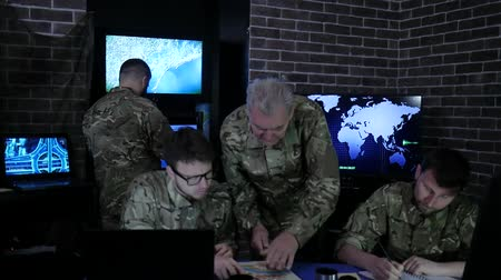 superior : experienced general beside from soldiers, in dispatch room, working process at briefing, discussing battle strategy, on background group people Military personnel at uniform near monitor screen