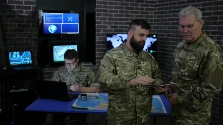 safeness : Military personnel, commander and soldier, in military headquarters, view digital tablet, discussing assault, security service and tracking terrorists, On background soldiers with map and laptop