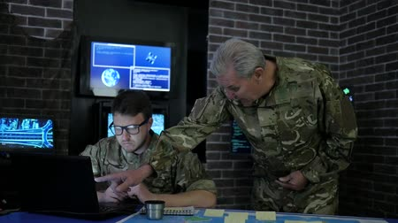 searches : chief and soldier in camouflage uniform, at briefing, in monitoring room, view maps, discussing assault, security service and tracking terrorists, on background display screens Stock Footage