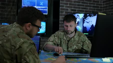 safeness : two soldiers working process, IT specialists, discussing battle strategy holding laptop, cyber safety briefing on background monitor, computer on military headquarter or war base, security service,