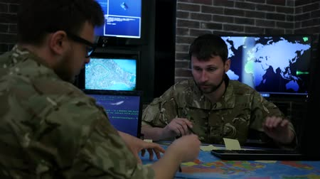 operators : Two soldiers IT specialists discussing battle strategy holding laptop, cyber safety briefing on background monitor, computer on military headquarter or war base, security service,