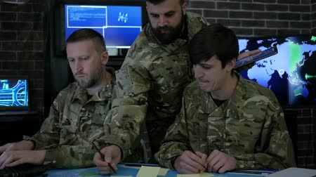 searches : team male security personnel are work with digital tablet and laptop, discussing battle strategy, security service, working in busy system control room, control apartment, on war base