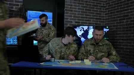 searches : squad IT specialists, cyber safety, discussing battle strategy holding digital tablet, briefing, on background monitor, laptop, computer, on military headquarter or war base, security service, Stock Footage