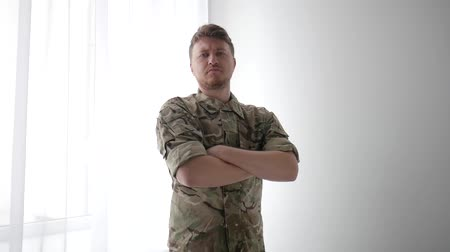 homecoming : portrait men warrior, handsome, strong, confident soldier, crossed his arms, camouflage uniform, military control, army, ground troops, armed forces on light background Stock Footage