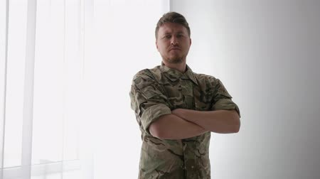 homecoming : portrait male soldier, strong, handsome, confident warrior, crossed his arms, camouflage uniform, military control, army, ground troops, armed forces on light background