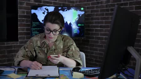 safeness : portrait female soldier with mobile phone, control center, war base, IT war, working process, cyber safety, technical control, tracking system, strategy warfare, field headquarters, military staff, attack and security Stock Footage