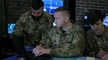 security agencies : employees security personnel work with digital tablet and laptop, discussing battle strategy, security service, working in busy system control room, control apartment, on war base