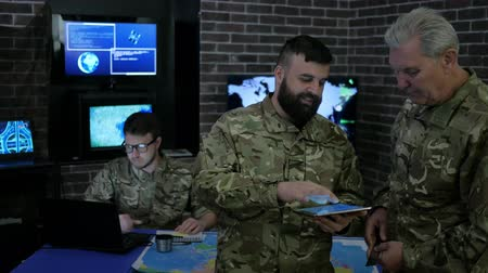 base station : discussing battle strategy and looking at digital tablet, security team, on background monitor, security service, control apartment, on war base, military inspection, soldiery headquarters Stock Footage