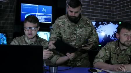 anti terrorism : director in uniform in monitoring room on war base, people beside computer and monitor screen, military headquarters, security service, group military IT professionals manages station,