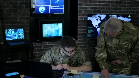 comando : commander indicates on map soldier, discussing battle strategy, security service, team security personnel working in busy system control room, control apartment, on war base, headquarters