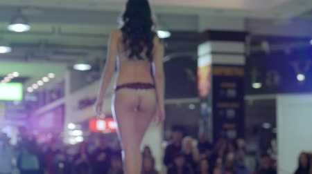 showcasing designs : model in lingerie and shoes go on podium, presentation style lingerie on fashion show, model in bikini and high heels going along catwalk, fashion business and style, slow motion