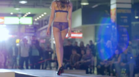 legs only : model in bikini and high heels going along catwalk, fashion business and style, model in lingerie and shoes go on podium, presentation style lingerie on fashion show, slow motion