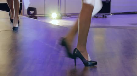legs only : legs in stylish black footwear, close-up of shoes on feets womens going along catwalk, collections shoes at fashion week, beautiful female legs in high heels during fashion show Stock Footage
