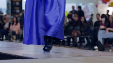 legs only : girl in evening dress and shoes go on podium, presentation new stylish clothes on fashion show, model in high heels going along catwalk, fashion business and style, slow motion