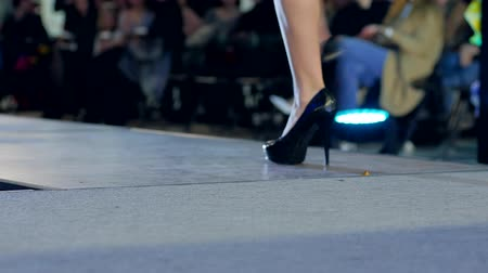 high heeled shoe : Fashion Defile Show, girl model goes on podium in light lamps, model in high heels on fashion show on catwalk, black shoes close-up, new of collections of womens clothing, dis-focused,