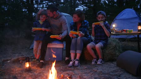opadavý : dinner near flames on nature, family eat corn with salt, travel camping, mama, daddy and sons eat up fresh yellow maize from out fire, at night in open air, journey with tents during summer holidays