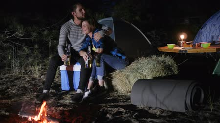coals : travel camp of men and female into woodland, romantic evening lovers with tents in forest, young couple drinking beer in journey with tents on nature, tourist trip of guy and girl at campground,
