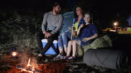 lampa naftowa : travel camp of american family in woodland, parents drink beer and child eats zephyr near bonfire in journey with tents, family trip on weekend in forest, mom and dad with son enjoy camping on nature,