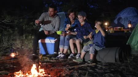 lampa naftowa : parents with children puts zephyr to skewer near campfire in woodland, family communicates and putting marshmallows on skewer near fire on nature, husband and wife with kids enjoying camping in forest, Wideo