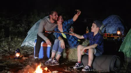 civakodás : mother and father with son photographed on android in nature near bonfire, happy family makes photo on mobile phone near campfire in forest, parents with child into travel camp make selfi photo,