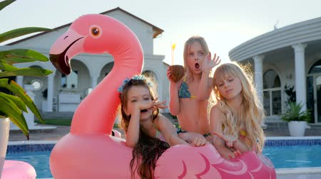 фламинго : sweet girls lie on inflatable pink flamingo near pool, spoiled rich childs in backlight outdoors, children have fun in background villa, kids celebrities in swimsuit on summer vacation