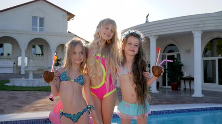 yakın : spoiled children posing on camera near pool and villa, kids celebrities in swimsuit on summer vacation, rich childs with cocktails in backlight, little girls with tropical cocktails Stok Video