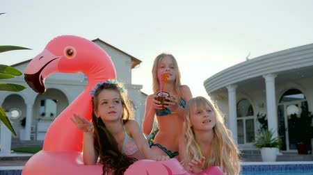 caráter : kids celebrities in swimsuit on summer vacation, little girls lie on inflatable pink flamingo near pool, spoiled rich childs in backlight, children have fun in background villa