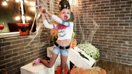 ameaça : having fun at halloween party, harley quinn threatens with baseball bat, happy little girl, halloween party celebration, kids halloween killer costume, masquerade at all saints day, trick or treat