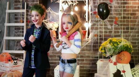 kanlı : children screaming, harley quinn and joker costumes, crazy characters, kids having fun at halloween party, spooky makeup, killers halloween costumes, masquerade at all saints day, trick or treat Stok Video
