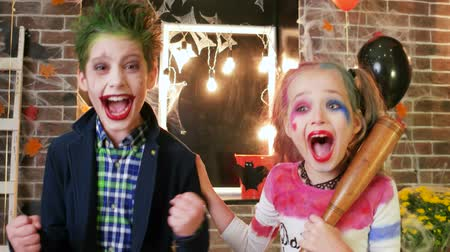 scary clown : harley quinn and joker screaming, kids having fun at halloween party, crazy characters, spooky makeup, children killers halloween costumes, baseball bat, masquerade at all saints day, trick or treat
