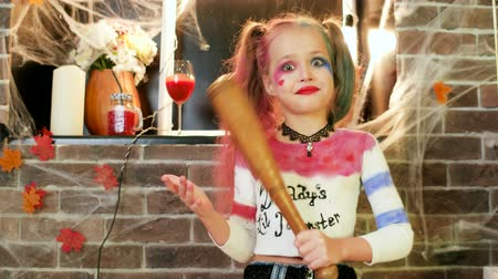 ameaça : little girl threatens with baseball bat, harley quinn character, dangerous child, halloween party celebration, kids halloween killer costume, masquerade at all saints day, trick or treat, horror night Stock Footage