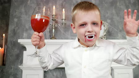 villain : vampire boy, child in dracula costume with glass of blood, halloween costume, dangerous child, thirsty vampire, halloween party decorations, masquerade at all saints day, time for trick or treat
