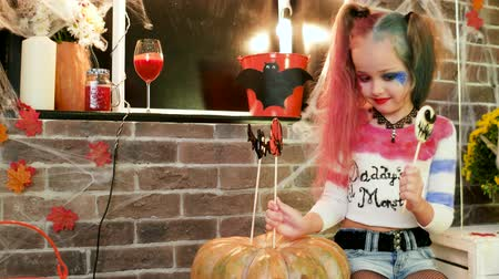 fruit bat : harley quinn decorating pumpkin with sweets, halloween costume, dangerous child, halloween party decorations, crazy character, masquerade at all saints day, time for trick or treat, autumn holiday Stock Footage