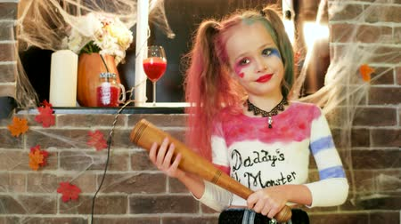 ameaça : harley quinn halloween costume, little girl playing crazy character, halloween party celebration, dangerous child, threatens with baseball bat, masquerade at all saints day, time for trick or treat