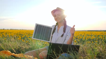 coletor : portrait girl shows sign approval and holds in hands solar panel in open air, female in backlight with notebook charger in arms, young woman near solar battery and laptop on field of sunflowers