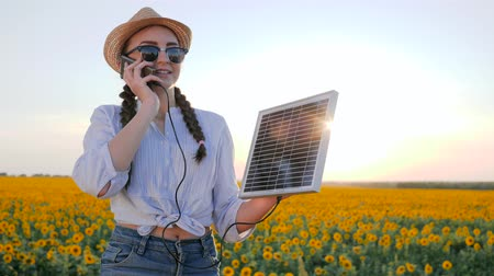 coletor : natural resources, woman in backlit talk mobile and keep solar battery tracking sun to charge battery, girl speaks by mobile phone and holds solar panel in background field of sunflowers
