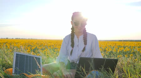 producing energy : natural energy, happy young woman applying solar photovoltaic panels outdoors, female in backlight with notebook charging from sun, girl recharges laptop using solar battery on field of sunflowers Stock Footage