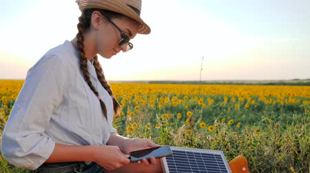 kolektor : girl using mobile and solar panel communicates in social network on background field, young woman browsing cellular phone uses solar battery, female with cellphone and battery
